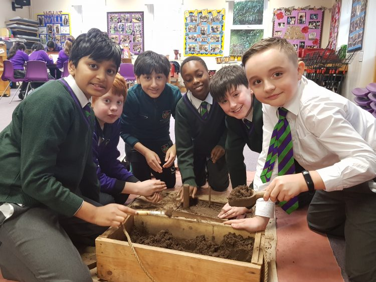 Pupils play with interactive learning tools during history lesson