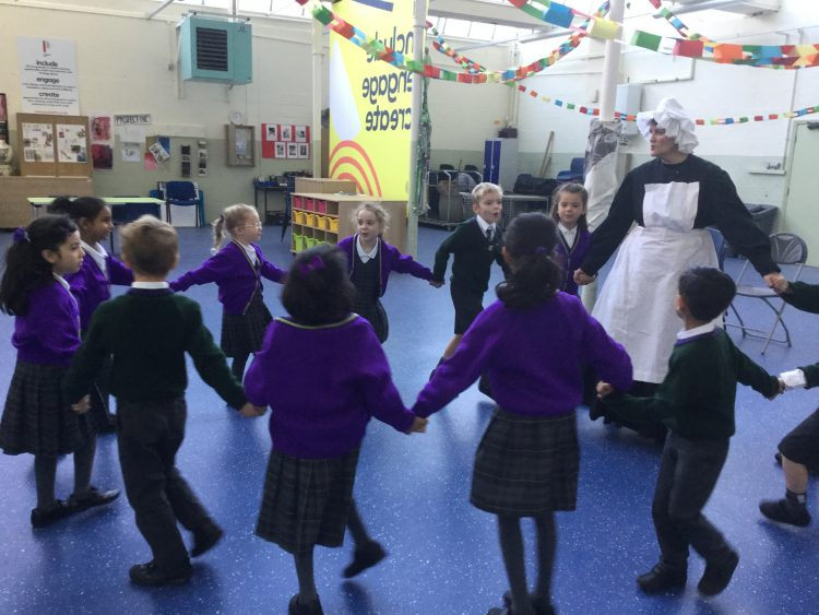 Westholme pupils dance in a circle at a Victorian Christmas experience at Queen Street Mill in Burnley