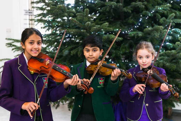 Three Westholme junior school pupils play their violins at the junior school carol service in Blackburn Cathedral