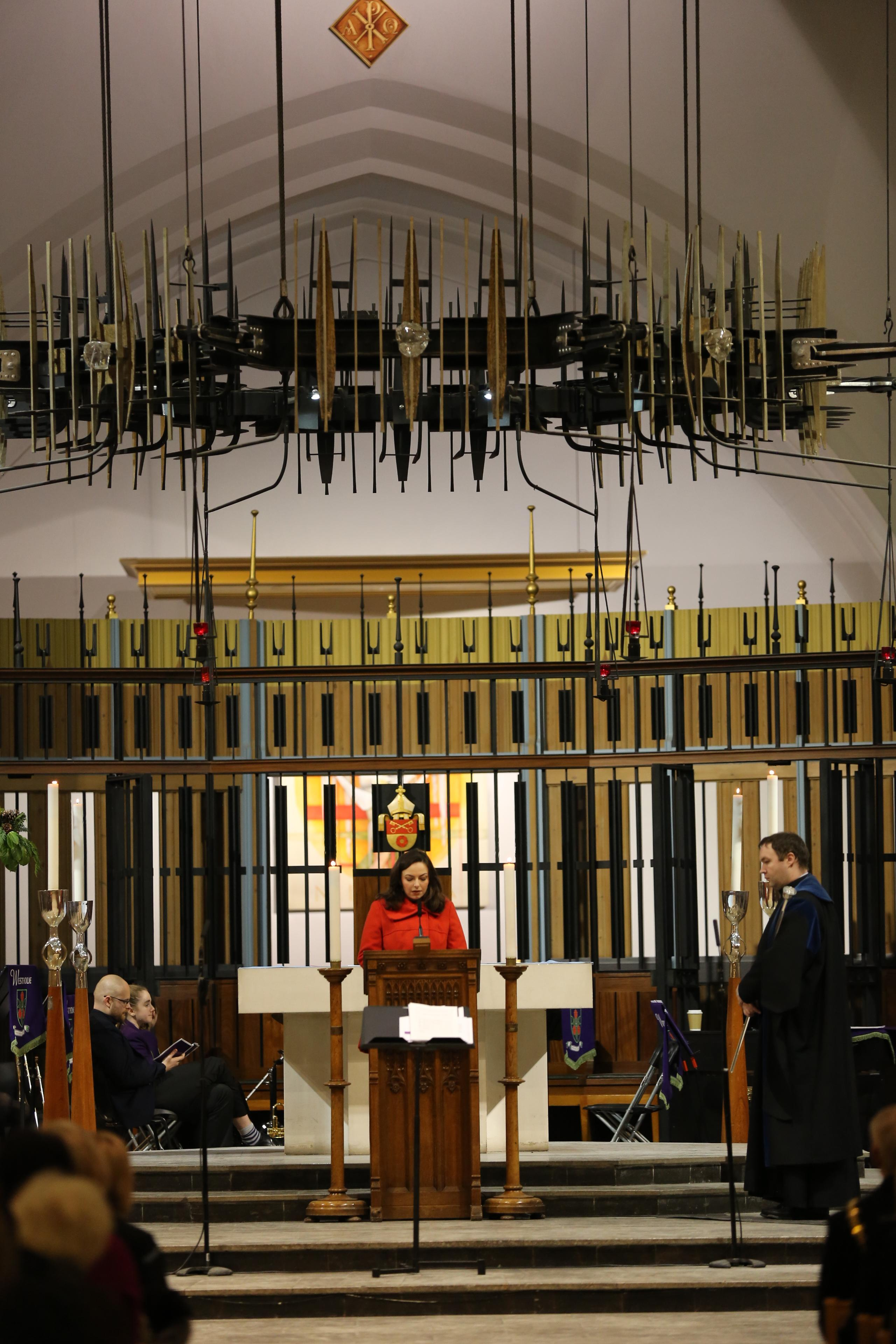 Woman performs reading at the Westholme senior school carol service at Blackburn cathedral