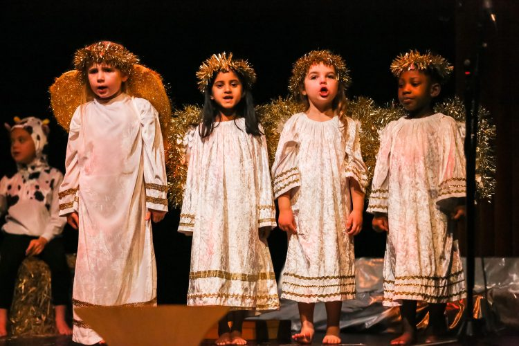 4 pupils dressed as angels sing at the Westholme Nursery and Infant school nativity play