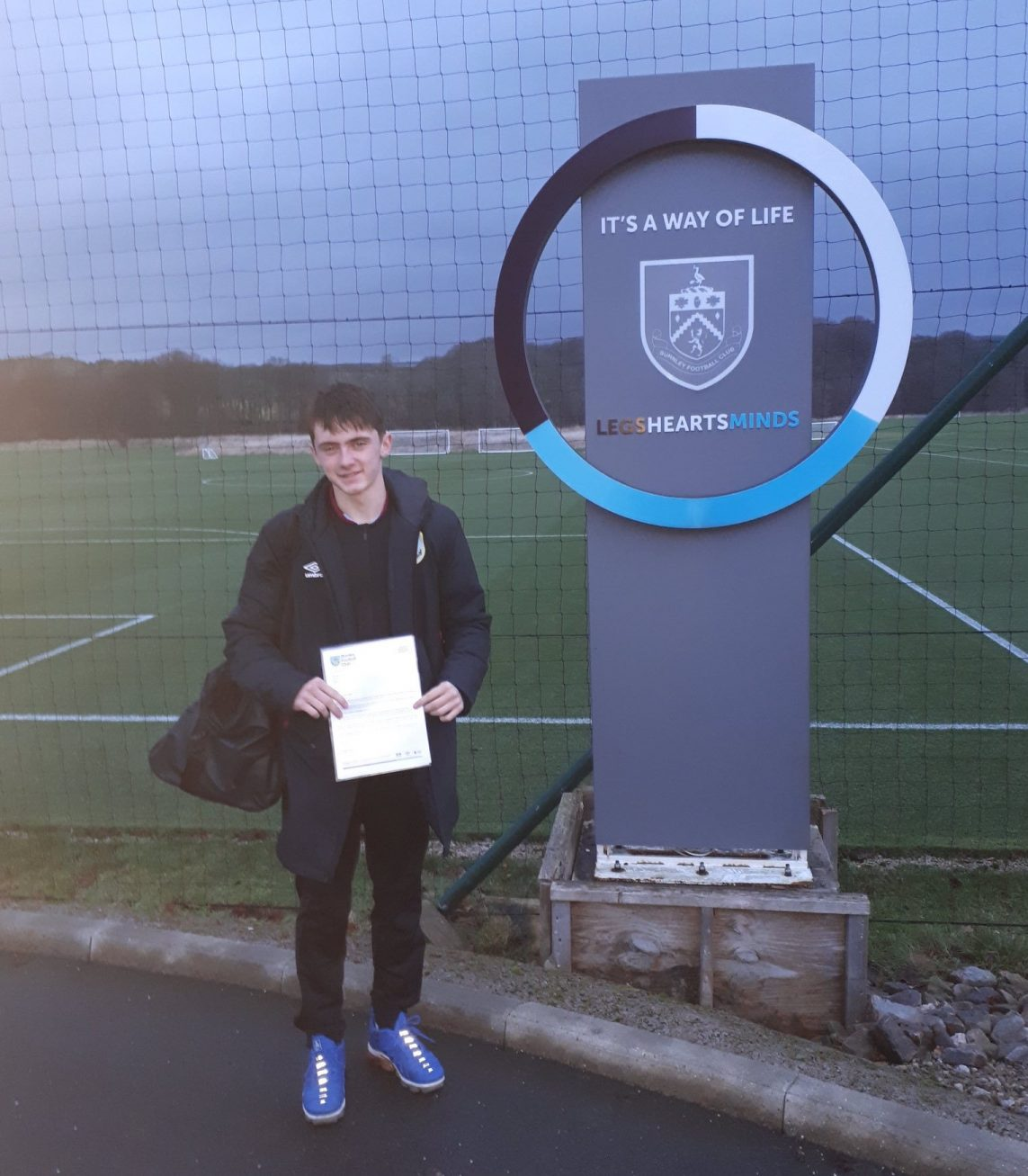 Westholme year 11 pupil Will Couch stands outside Burnley FC training ground with club scholarship letter
