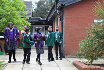Year 7's discuss a treasure hunt with their teacher outside the school building 2